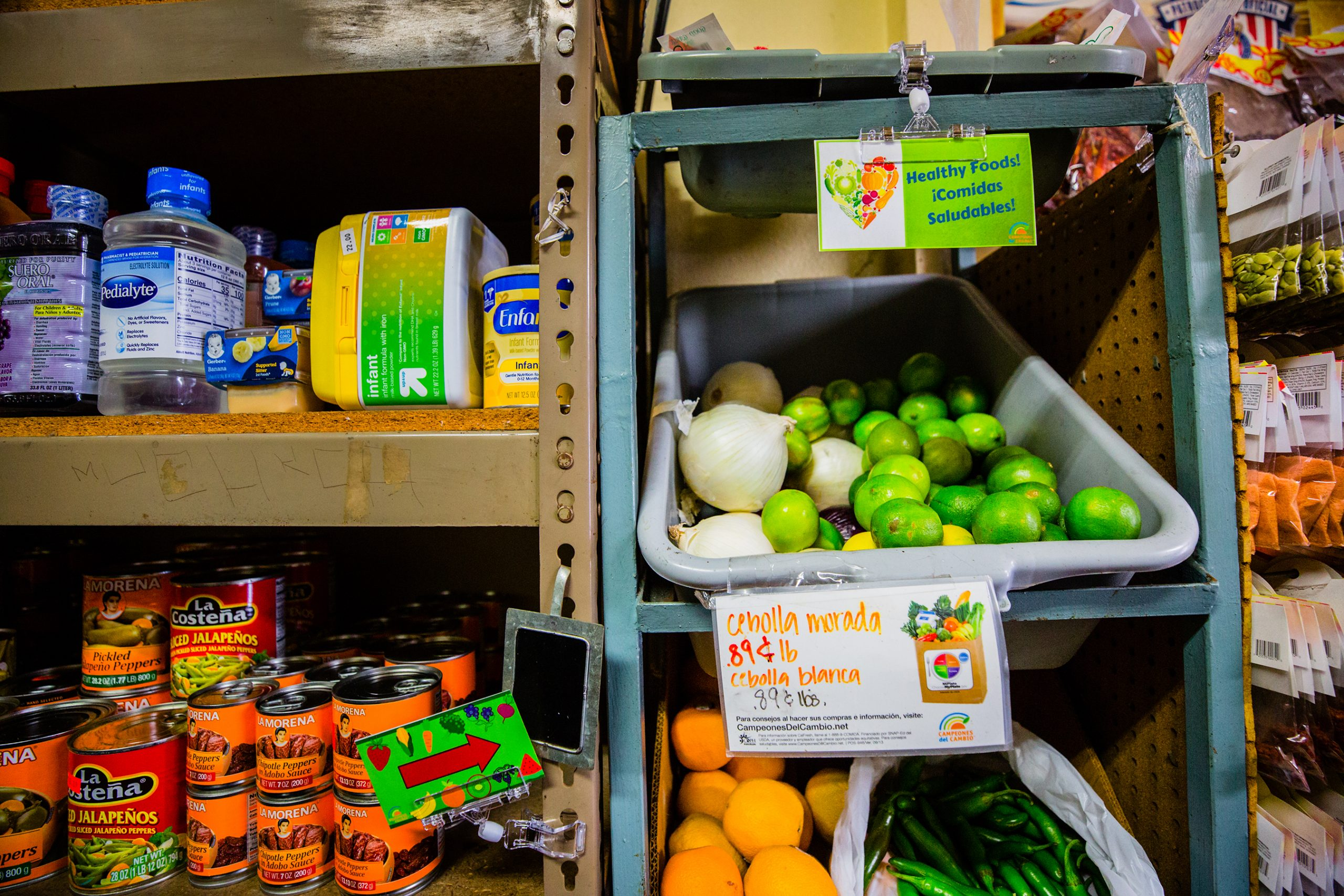 a picture of grocery store shelves stocked with vegetables and canned food