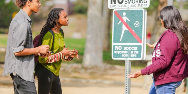 Three students review signage at an outdoor park that prohibits soccer, smoking and fires.