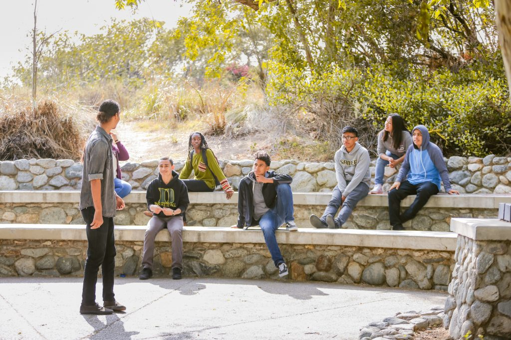 A picture of students in an outdoor park seated and facing one student who is standing and talking to them.