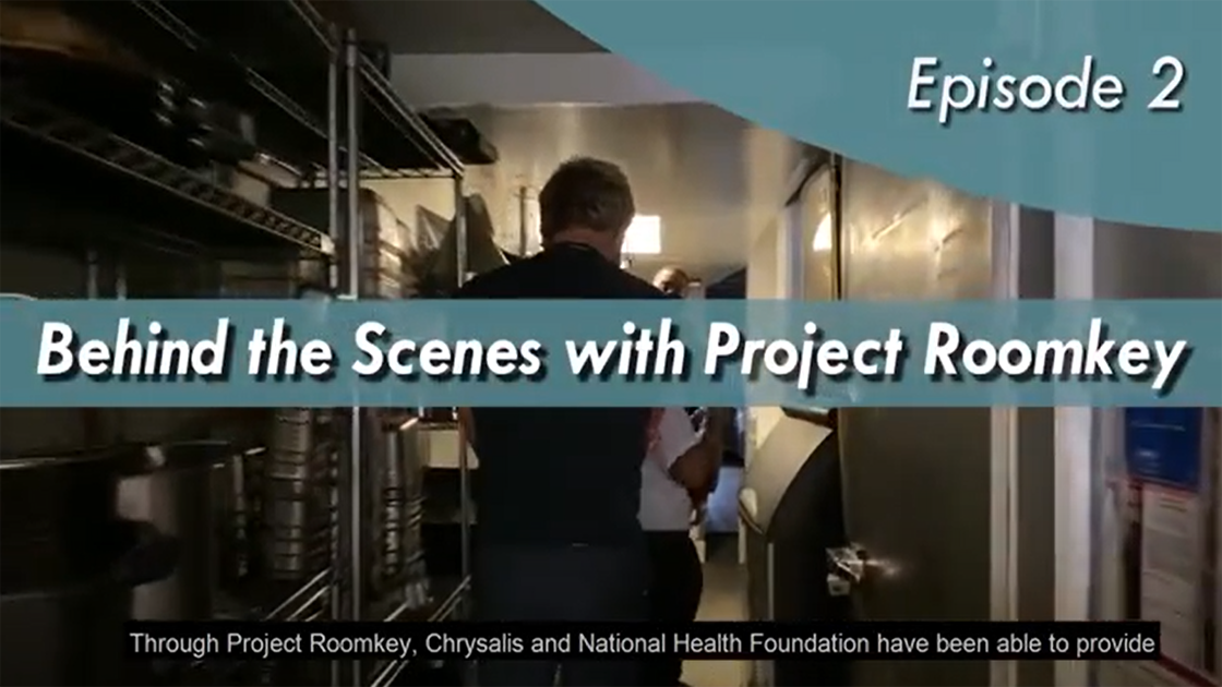 A video screenshot with text overlay: behind the scenes with Project Roomkey with staff walking down a hallway.
