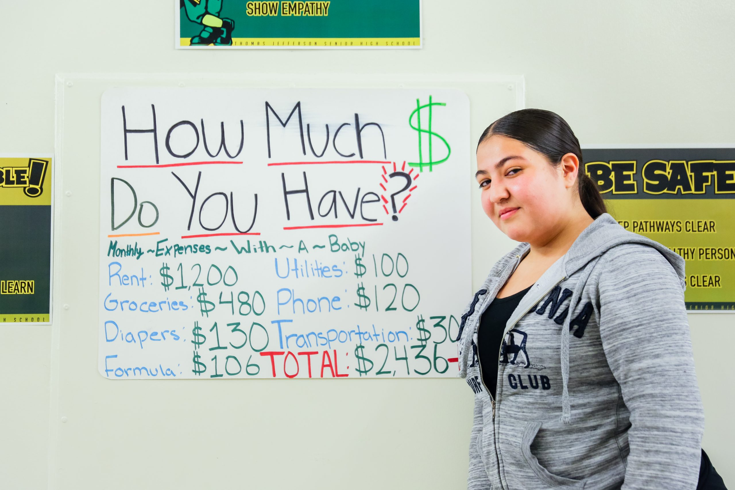 "A picture of a teen standing in front of a poster that reads ""How much money do you have?"""
